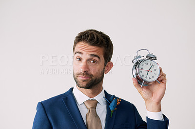 Buy stock photo Studio shot of a handsome young groom holding a clock against a gray background