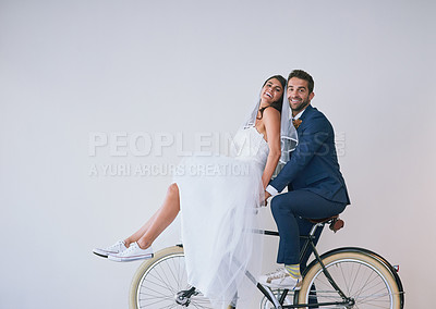 Buy stock photo Studio shot of a newly married young couple riding a bicycle together against a gray background