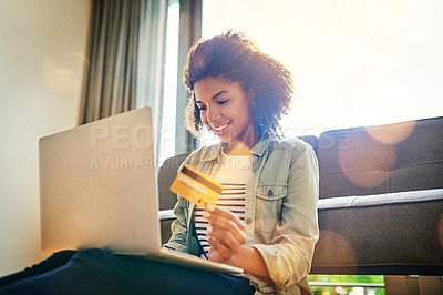 Buy stock photo Shot of a cheerful young woman doing online shopping on her laptop while being seated on the floor at home