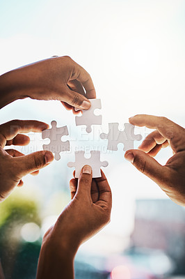 Buy stock photo Cropped shot of businesspeople completing a puzzle together in a modern office
