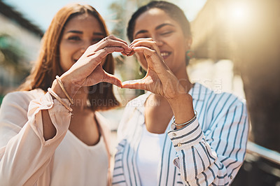 Buy stock photo Shot of two cheerful young women forming a heart shape with their hands together while standing outside during the day