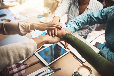 Buy stock photo Shot of an unrecognizable group of work colleagues forming a huddle together with their hands while being seated at a table together