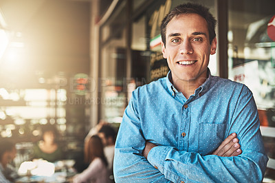 Buy stock photo Portrait of a confident young man standing with his arms folded inside of a coffeeshop during the day