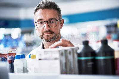 Buy stock photo Shot of a mature pharmacist checking products in a pharmacy