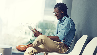 Buy stock photo Shot of a young businessman using a tablet while waiting for an interview