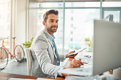 Buy stock photo Shot of a handsome young businessman working on a laptop and digital tablet in an office