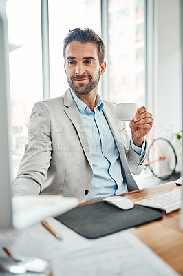 Buy stock photo Shot of a handsome young businessman drinking coffee while working on a laptop in an office