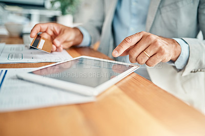 Buy stock photo Closeup shot of an unrecognizable businessman using a digital tablet while holding a credit card in an office