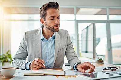 Buy stock photo Shot of a handsome young businessman writing notes while using a digital tablet in an office