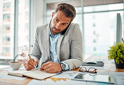 Buy stock photo Shot of a handsome young businessman writing notes while talking on a cellphone in an office