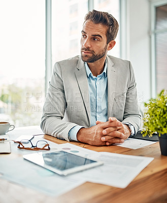 Buy stock photo Shot of a handsome young businessman sitting in an office