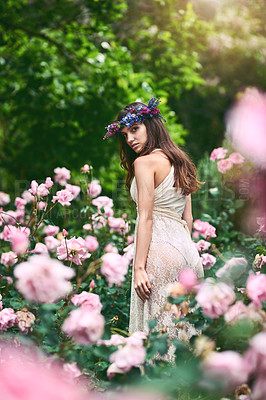 Buy stock photo Shot of a beautiful young woman wearing a floral head wreath posing in nature
