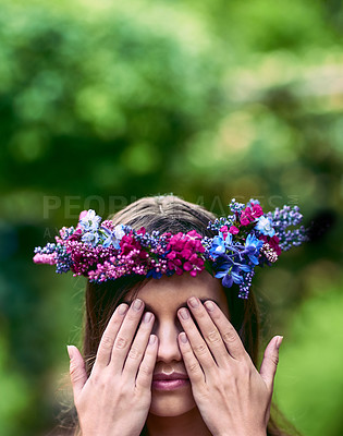 Buy stock photo Cropped shot of a beautiful young woman wearing a floral head wreath and covering her eyes in nature