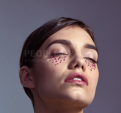 Buy stock photo Studio shot of an attractive young woman with gems under her eyes posing against a purple background