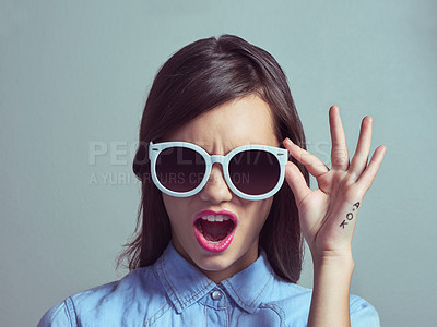 Buy stock photo Studio portrait of an attractive young woman looking shocked while wearing shades against a grey background