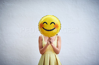 Buy stock photo Studio shot of a young woman holding a balloon with a smiley in front of her face
