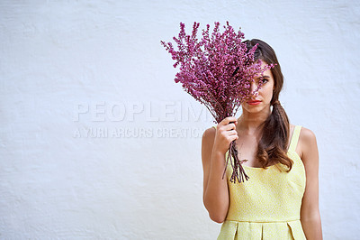 Buy stock photo Studio portrait of a confident young woman hiding behind a bouquet of flowers while standing against a grey background