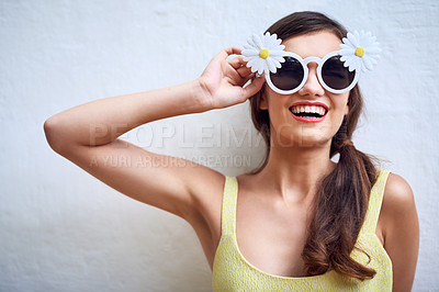 Buy stock photo Studio portrait of a cheerful young woman wearing sunglasses while posing against a grey background