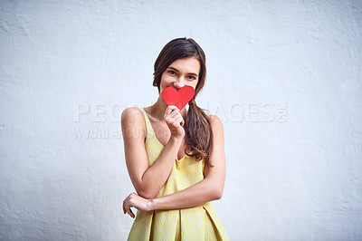 Buy stock photo Studio shot of a cheerful young woman holding a heart shaped piece of paper in her hands while standing against a grey background