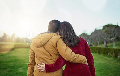 Buy stock photo Rearview shot of a young couple embracing each other outdoors