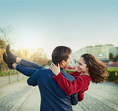 Buy stock photo Shot of a young man romantically carrying his girlfriend outdoors
