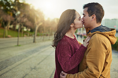 Buy stock photo Shot of a happy young couple kissing each other outdoors