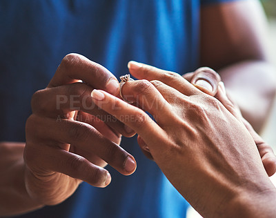 Buy stock photo Closeup shot of an unrecognizable man putting an engagement ring onto his fiancee's finger