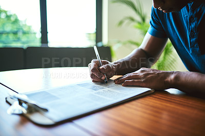 Buy stock photo Closeup shot of an unrecognizable man filling in paperwork at a table