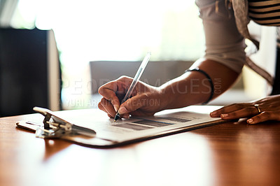 Buy stock photo Closeup shot of an unrecognizable woman filling in paperwork at a table