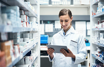 Buy stock photo Cropped shot of a young female pharmacist using a tablet while working in a dispensary