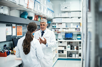 Buy stock photo Cropped shot of two pharmacists working together in a dispensary