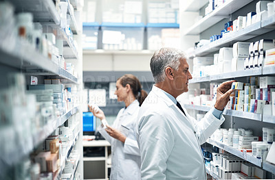 Buy stock photo Cropped shot of two pharmacists checking products while working together in a dispensary