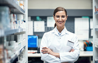 Buy stock photo Cropped portrait of a young female pharmacist standing with her arms folded while working in a dispensary