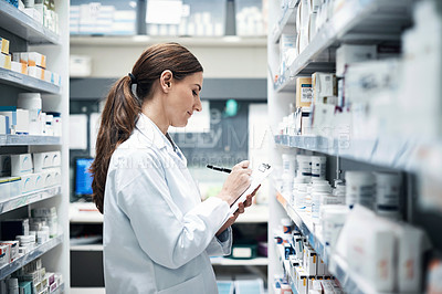 Buy stock photo Cropped shot of a young female pharmacist doing stock take while working in a dispensary