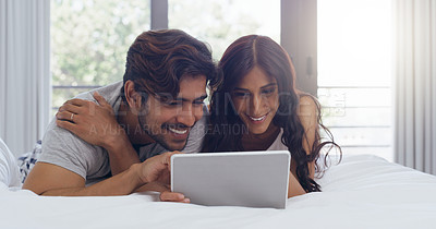 Buy stock photo Shot of a young attractive couple using a tablet together in the bedroom at home