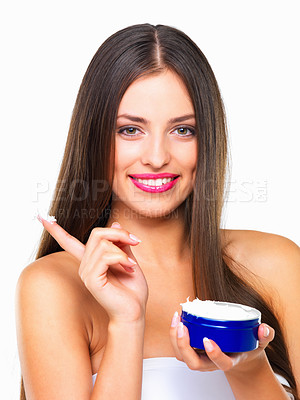 Buy stock photo Studio portrait of a beautiful young woman applying lotion against a white background