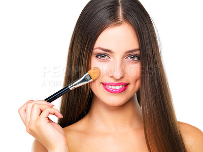 Buy stock photo Studio portrait of a beautiful young woman applying blush against a white background