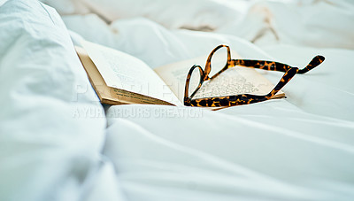 Buy stock photo Still life shot of a book and a pair of spectacles on a bed