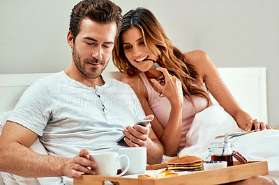 Buy stock photo Shot of a happy young couple using a cellphone while enjoying breakfast in bed together at home
