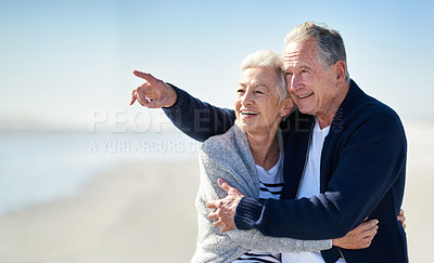 Buy stock photo Shot of a happy senior man showing his wife something at the beach