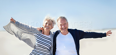 Buy stock photo Portrait of a happy senior couple having fun with their arms outstretched at the beach