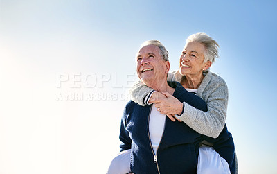 Buy stock photo Shot of a happy senior couple enjoying a piggyback ride outdoors