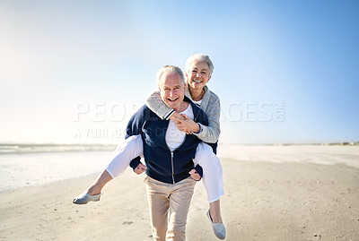 Buy stock photo Portrait of a happy senior couple enjoying a piggyback ride at the beach