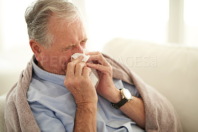 Buy stock photo Shot of a senior man blowing his nose with a tissue at home