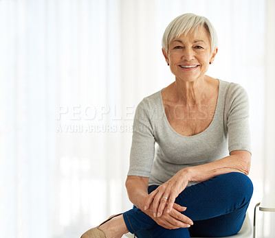 Buy stock photo Shot of a confident senior woman relaxing on a chair at home