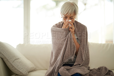 Buy stock photo Shot of a senior woman blowing her nose with a tissue at home
