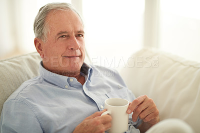 Buy stock photo Shot of a senior man enjoying a relaxing coffee break on the sofa at home