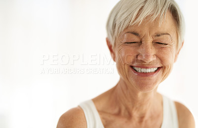 Buy stock photo Shot of an attractive senior woman laughing at home