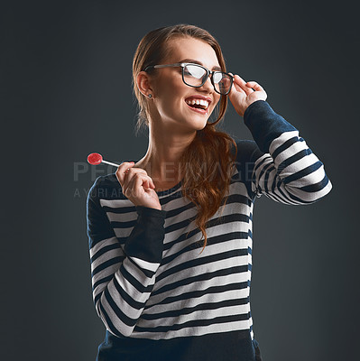 Buy stock photo Studio shot of a cheerful young woman wearing glasses and holding a lollypop while standing against a dark background