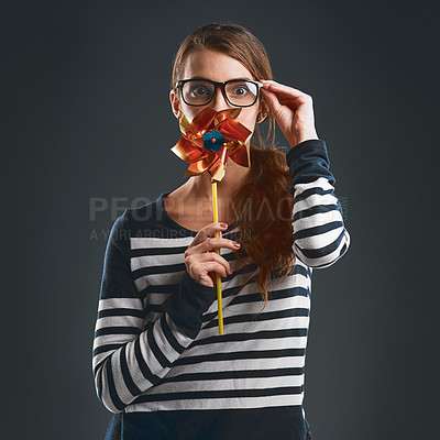 Buy stock photo Studio portrait of an attractive and playful young woman holding a pinwheel and blowing it while standing against a dark background